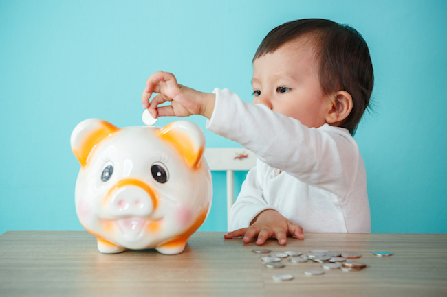 little baby moneybox putting a coin into a piggy bank - kid saving money